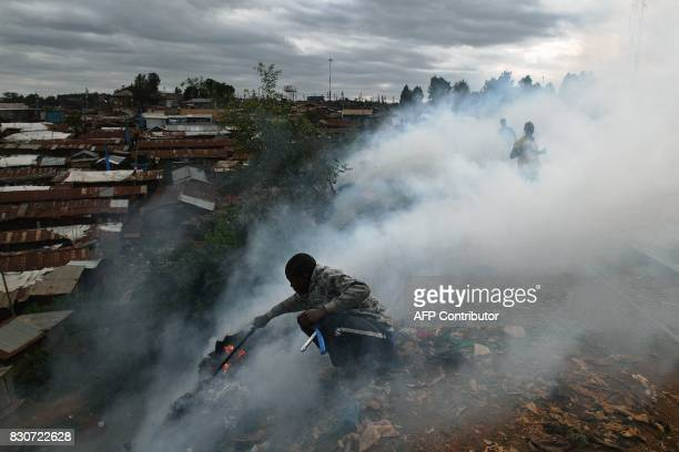 TOPSHOT A boy with a stick tries to save belongings from a fire in the Kibera slum in Nairobi on August 12 2017 Three people including a child have...