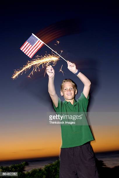 Boy with American flag and sparkler