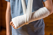 Boy with an arm in plaster in the brown background, accident at home , injury, trauma concept
