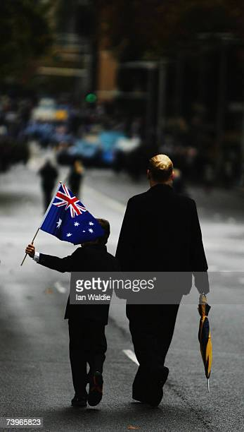 A boy with an Australian flag walks down the street during the Anzac day march April 25 2007 in Sydney Australia Australians and New Zealanders today...