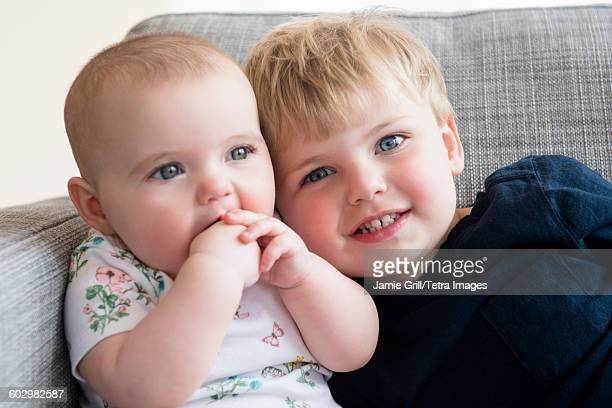 Boy (2-3) with baby sister (12-17 months) sitting on sofa