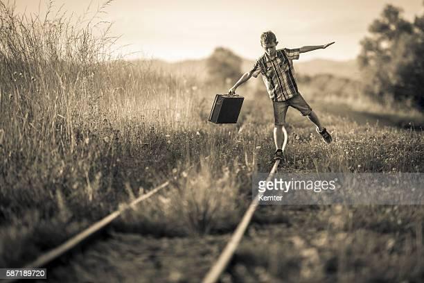 boy with bag balancing on rails