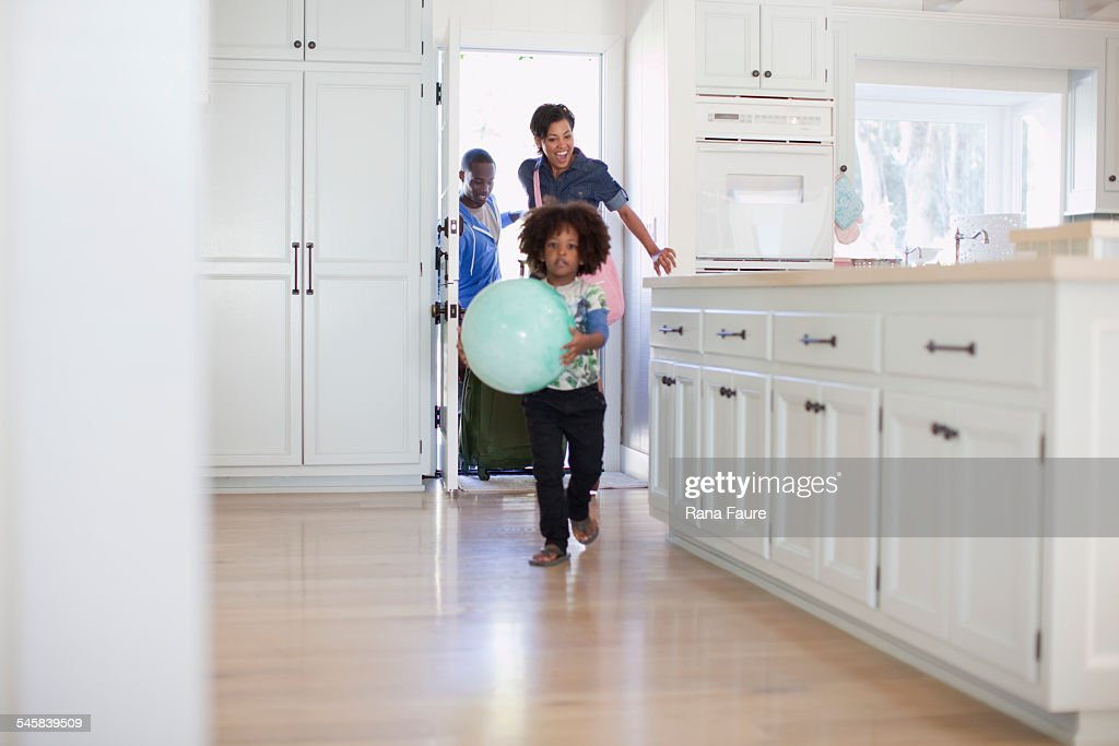Boy (5-6) with ball in kitchen, parents entering in background