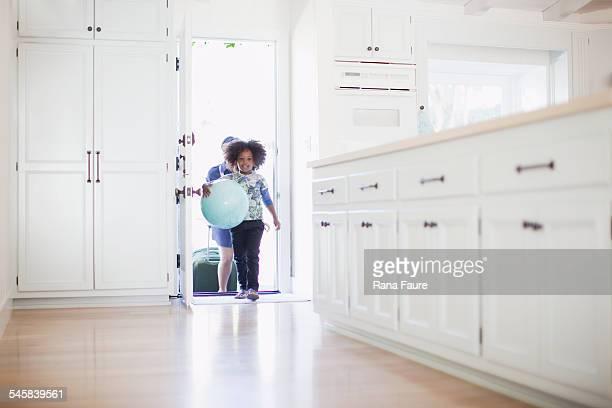 Boy (10-12) with ball on walking into open door