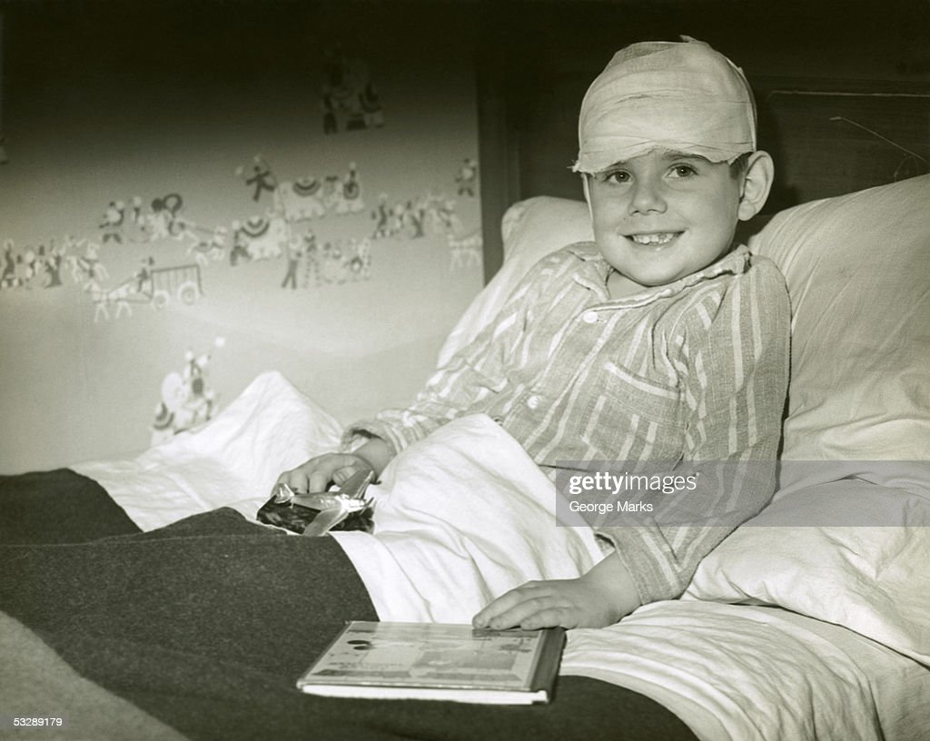 Boy with bandage on head, resting in bed : Stock Photo