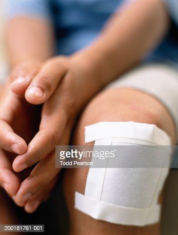 Boy (6-8) with bandage on knee, mid section (focus on bandage) : Stock Photo