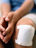 Boy (6-8) with bandage on knee, mid section (focus on bandage)