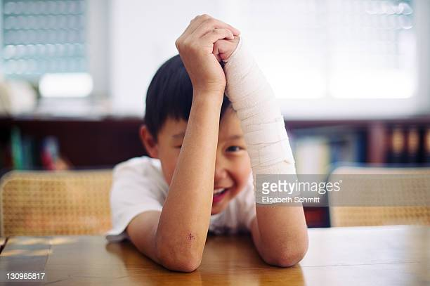 Boy with bandaged arm laughing in his home