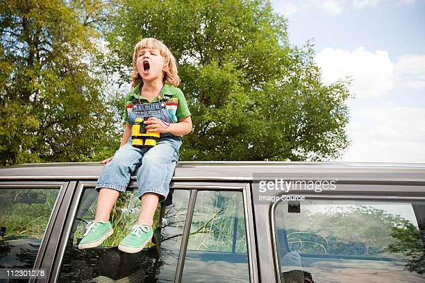 Boy with binoculars, sitting on roof of car