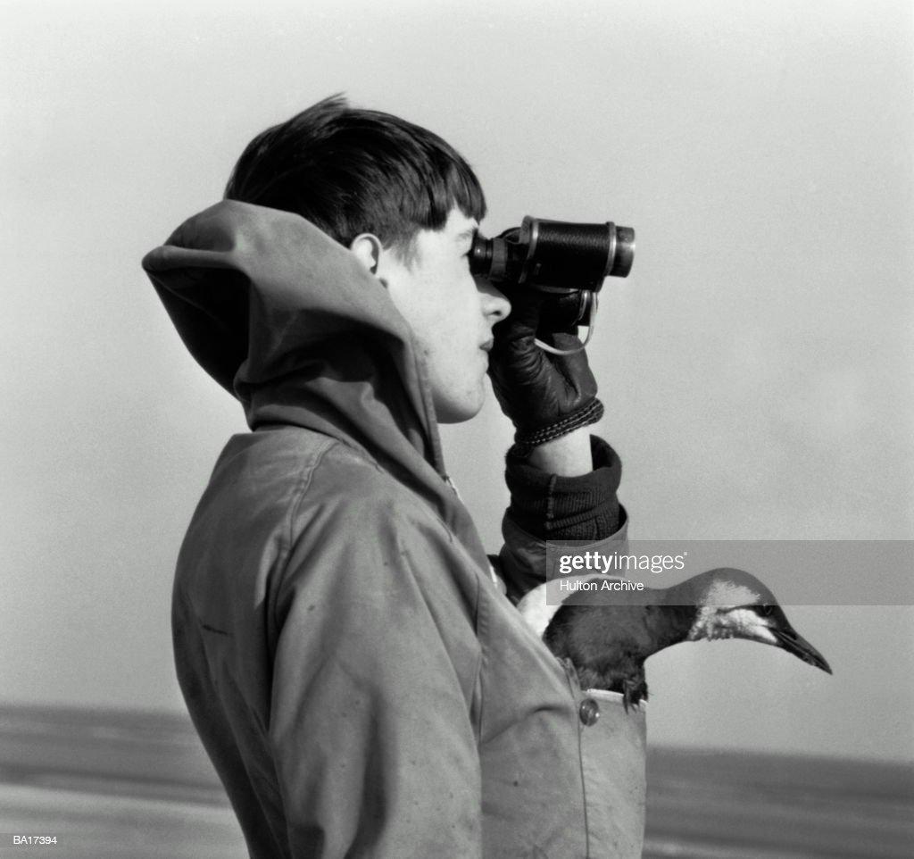 Boy (15-17) with bird in pocket looking through binoculars