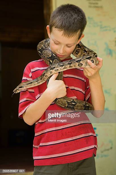 Boy (7-9) with boa constrictor around neck
