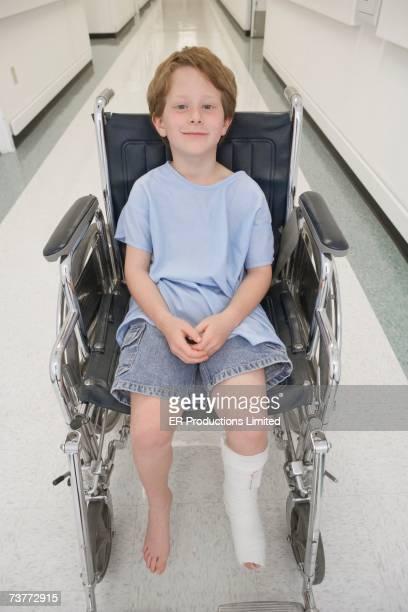 Boy with broken let sitting in wheelchair in hospital corridor