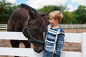 Smiling boy meets with the brown horse