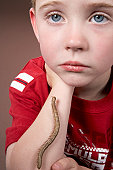 Boy (6-7) with caterpillar crawling on arm, close-up