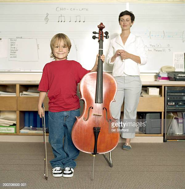 Boy (5-7) with cello, standing in front of music teacher in classroom