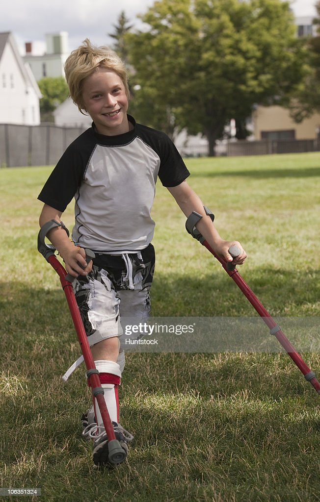 Boy with cerebral palsy walking with the support of crutches