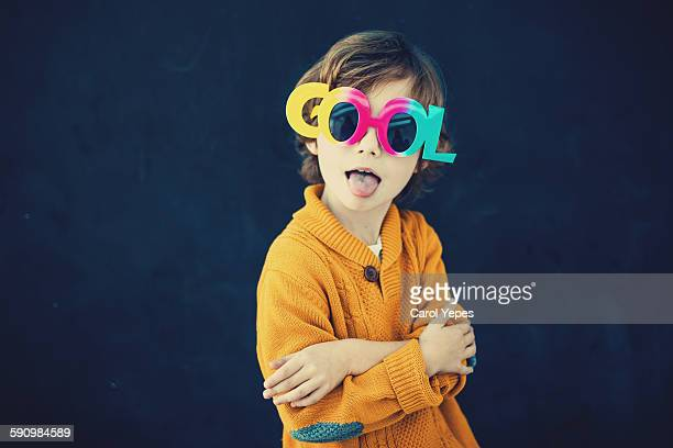 Boy with cool glasses sticking out tongue