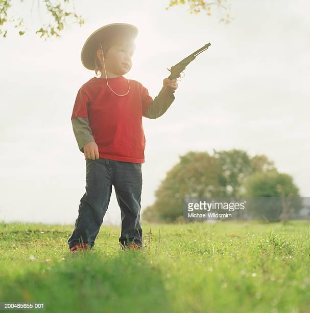 Boy (2-3) with cowboy hat holding toy gun