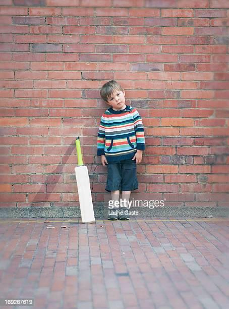 Boy with cricket bat against brick wall