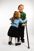 Boy with crutches being hugged by sister
