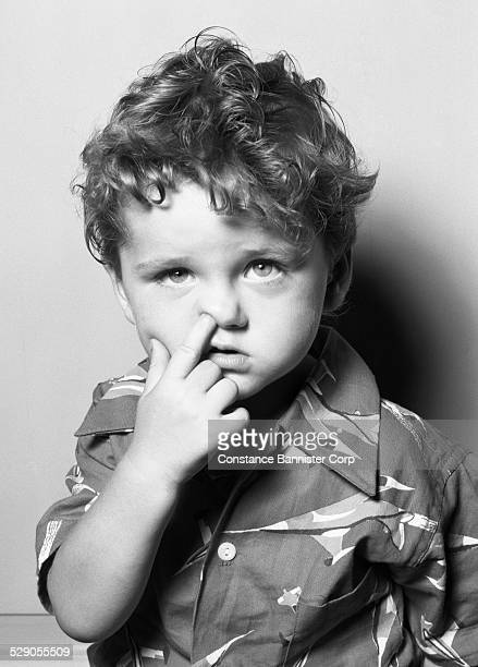 Boy with curly hair and one finger in nose