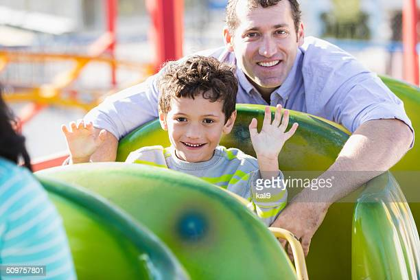 Boy with dad at amusement park on rollercoaster