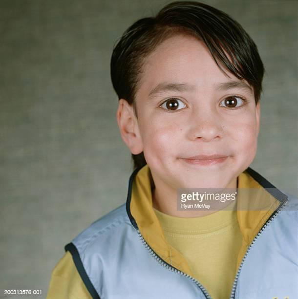 Boy (6-7) with dark brown eyes, smiling, portrait