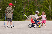 Boy with degenerative disease using crutches looking at a boy on tricycle with joint problems