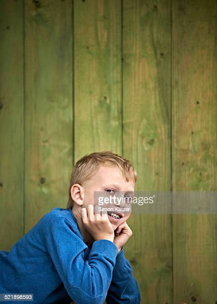 Boy with dental brace lying before wooden panels