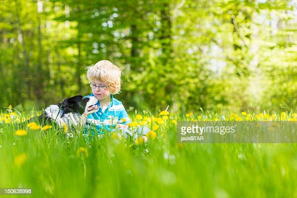 Boy with dog in field of tall grass