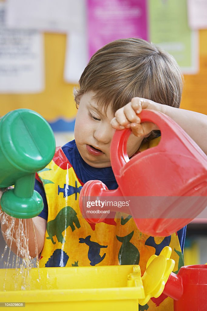 Boy (5-6) with Down syndrome playing with watering cans in kindergarten