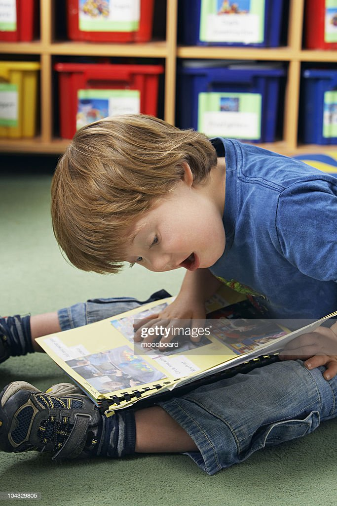 Boy (5-6) with Down syndrome reading book in kindergarten