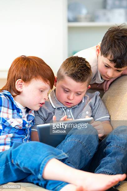 Boy With Downs Syndrome And Friends Using Digital Tablet