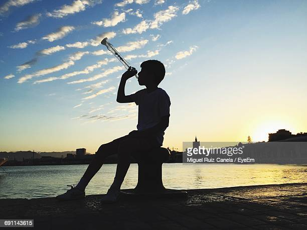 Boy With Drink While Sitting On Bollard At Pier During Sunset