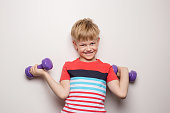 Boy with dumbbells over white background. Studio portrait