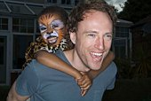 Boy with face paint riding piggyback on man