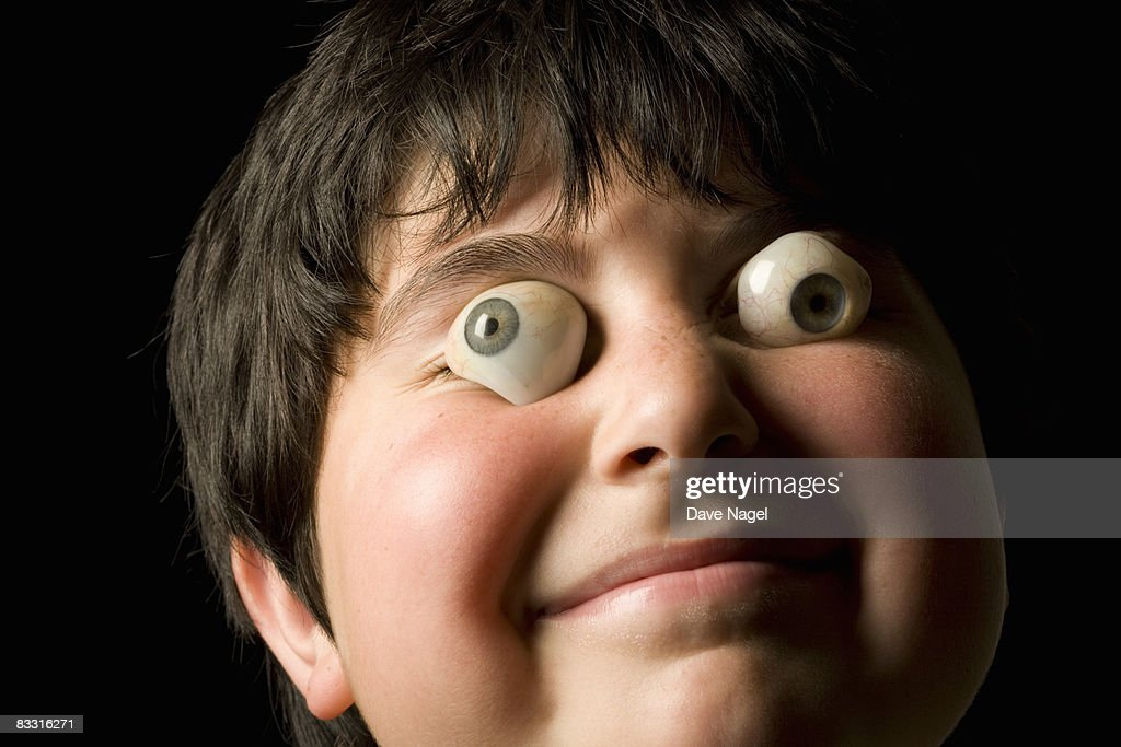 Boy with fake eyeballs in front of his eyes : Stock Photo
