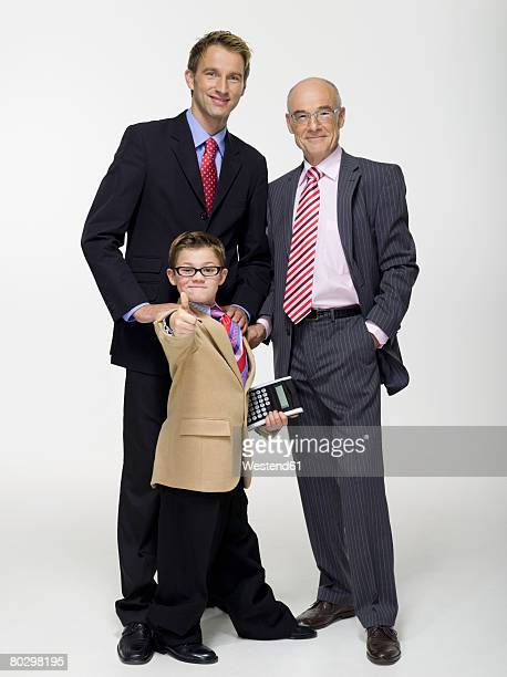 Boy (8-11) with father and grandfather holding calculator and giving thumbs up, portrait