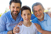 Boy with father and grandfather outdoors