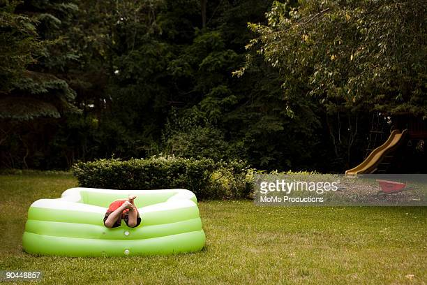 boy (4-5) with feet sticking out of baby pool