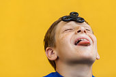 Young beautiful happy boy with freckles blue t-shirt holding fidget spinner on yellow background.