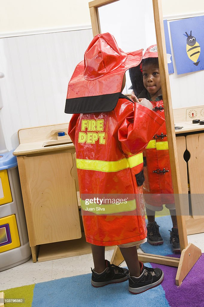 Boy with fireman costume looking at mirror