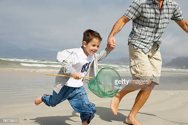 Boy with Fishing Net Running on Beach with Father