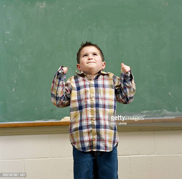 Boy (3-5) with fists closed standing in front of blackboard