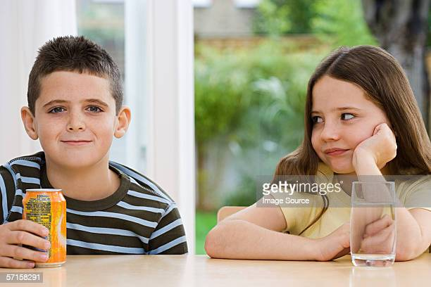Boy with fizzy drink and girl with water
