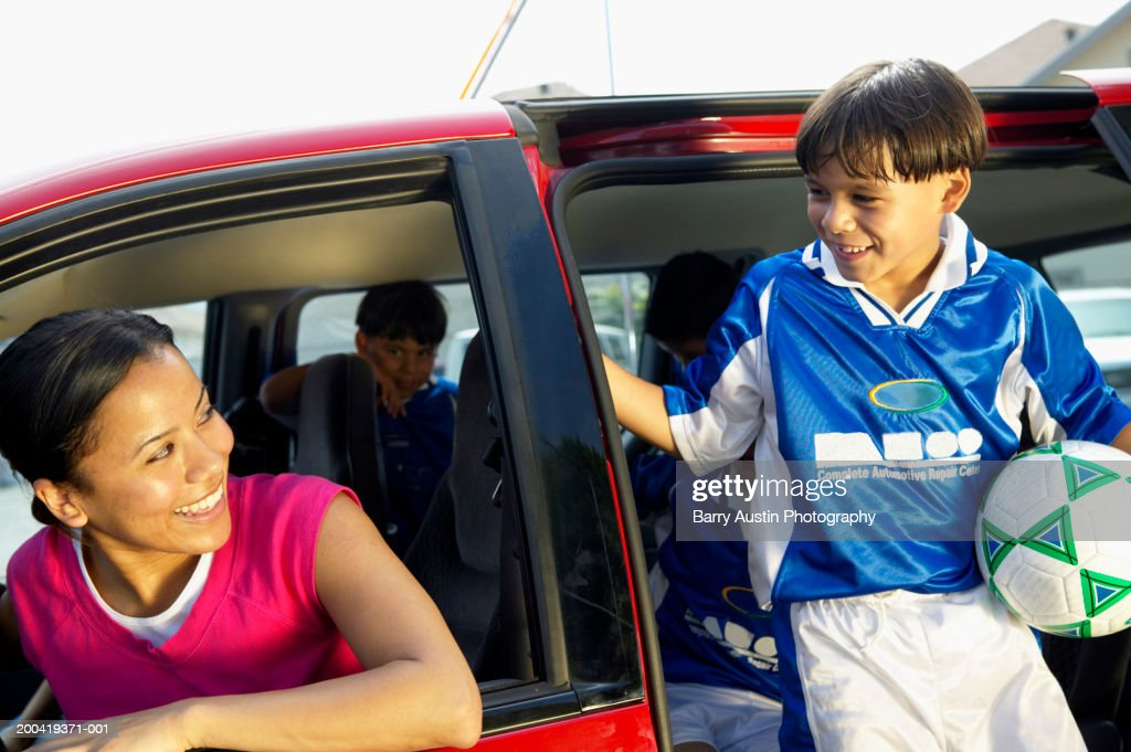 Boy (7-9) with football getting out of car, smiling at woman in car