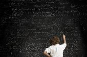 Boy with formulae on blackboard