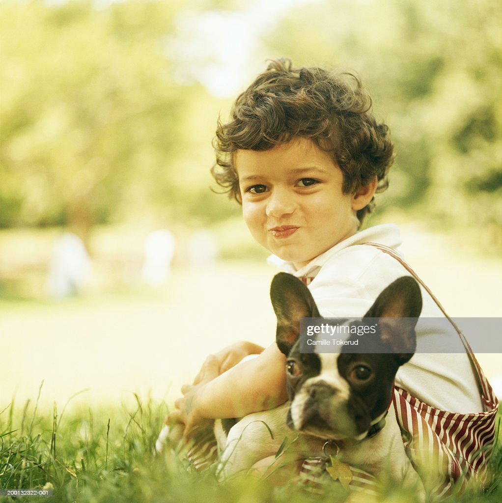 Boy (3-5) with French bulldog in park : Stock Photo