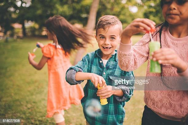 Junge mit gap, deren Zahnlücken Lächeln spielen mit Blasen und Freunde