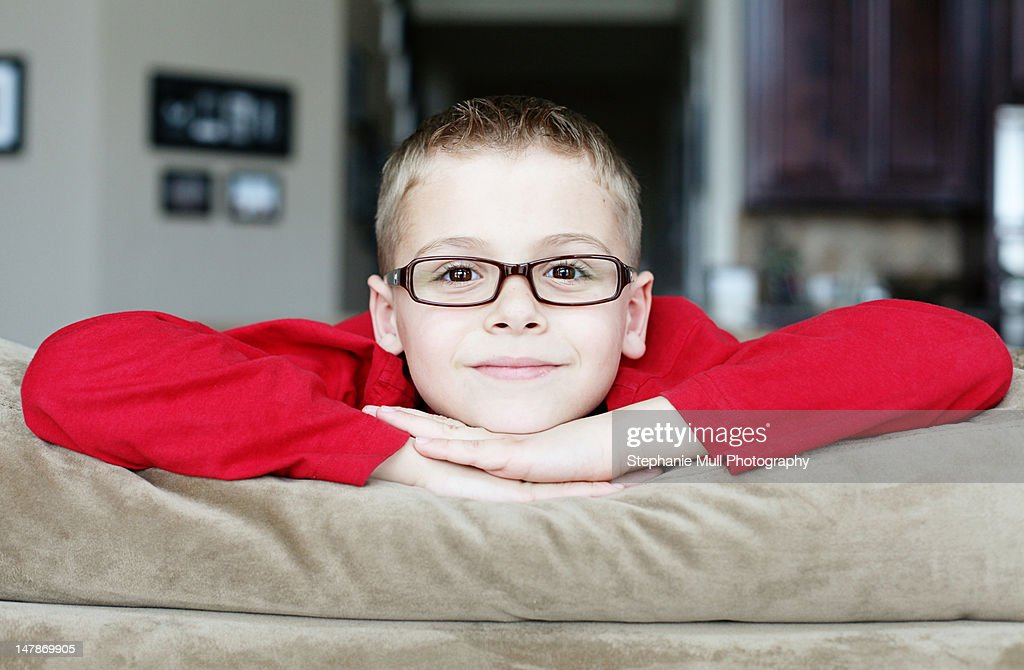 Boy with glasses resting head on hands : Stock Photo